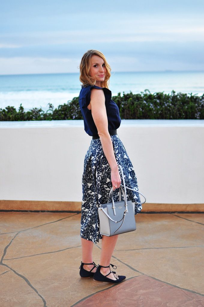 Lace-up flats, patterned midi skirt, ruffled blouse, Kate Spade tote.