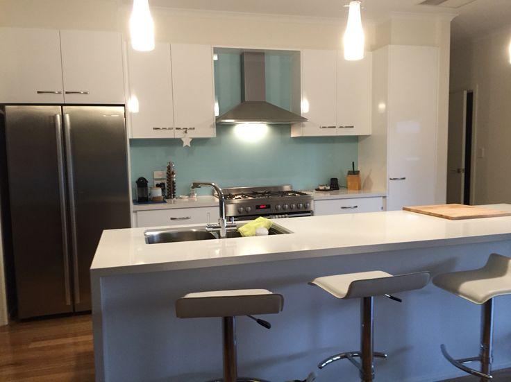 Modern white high gloss kitchen with island bench. Glass splash back. Essa stone bench tops.