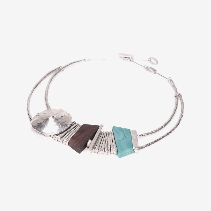 Obis - 2017 Obis is an enchanting princess-length necklace with a stunning design sure to cast a spell on any viewer. It is made up of hand-hammered pewter pendants, fanning metal bars, an aqua glass stone, and wooden bead.