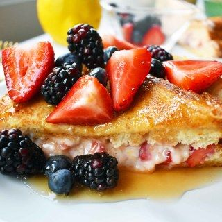 Strawberries and Cream French Toast. Sweet cream cheese, jam and fresh strawberries stuffed between two pieces of soft Texas toast. Dipped into a rich custard batter and cooked until golden brown in skillet. Gourmet french toast made in less than 15 minutes. Perfect topped with fresh berries and homemade whipped cream. www.modernhoney.com