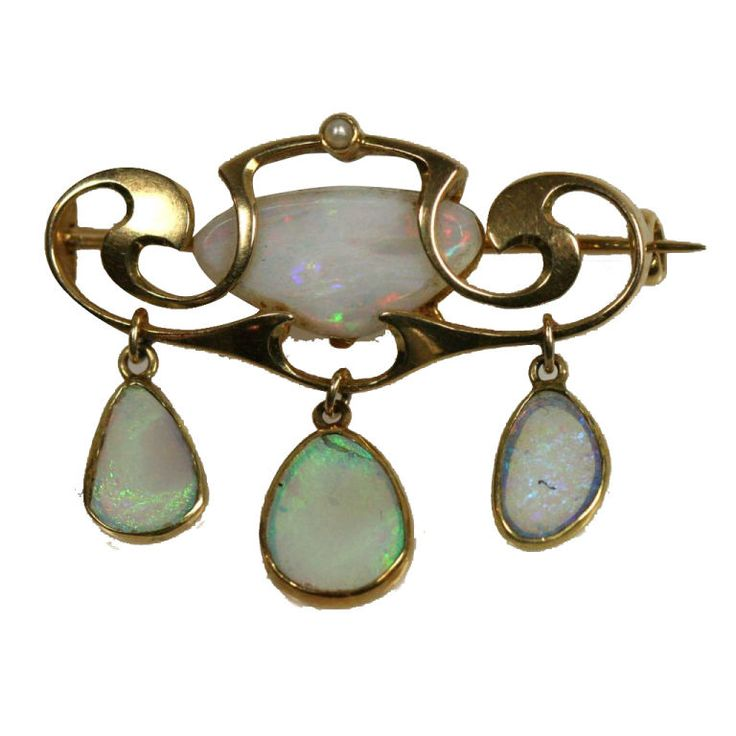 """English Arts & Crafts period 15 carat gold and opal brooch by Liberty of London. Designed by Archibald Knox for the Murrle Bennett & Co circa 1910-15. This brooch features a curvelinear setting for a central white opal and three opal drops. This is a wonderful example of Knox's work. The piece measures 1 1/4"""" wide by 1 1/8"""" high and bears impressed company marks."""