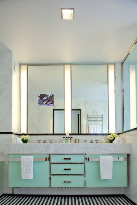 This NYC bathroom has black and white tile flooring, marble walls, marble countertop, light teal cabinets, chrome trim, dual vanities, and linear light fixtures.
