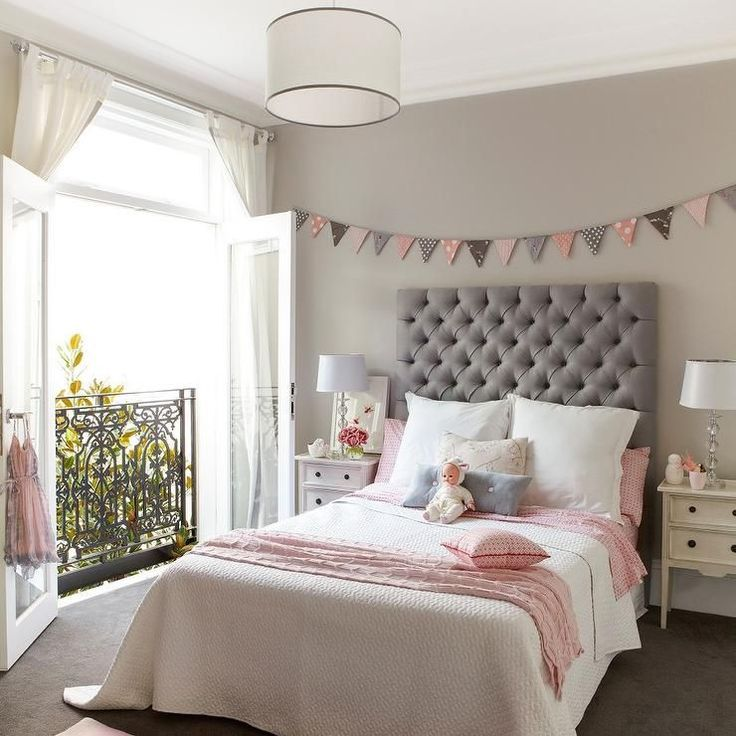 Pink and gray girl's room features walls painted a warm gray lined with a pink and gray banner placed over a gray velvet tufted headboard on full bed dressed in white and pink bedding flanked by cream French nightstands illuminated by a white drum pendant with gray ribbon trim.