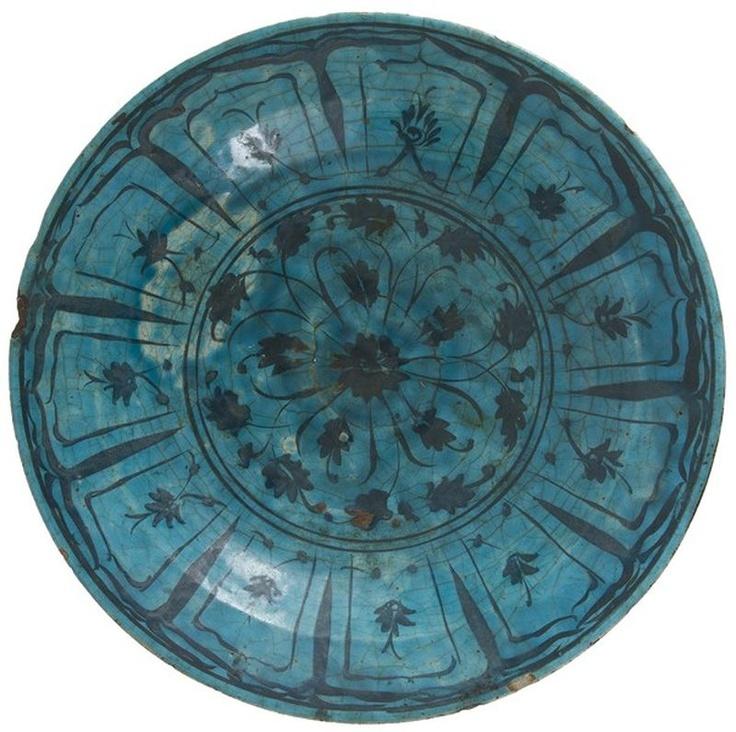 Grand plat à la rosette, Iran, Koubatcha, XVIIe siècle Céramique siliceuse à décor peint en noir sous glaçure turquoise. Large rosette cernée d'une frise de feuilles digitées, et bordée de larges pétales arqués agrémentés de palmes. D. : 34,5 cm