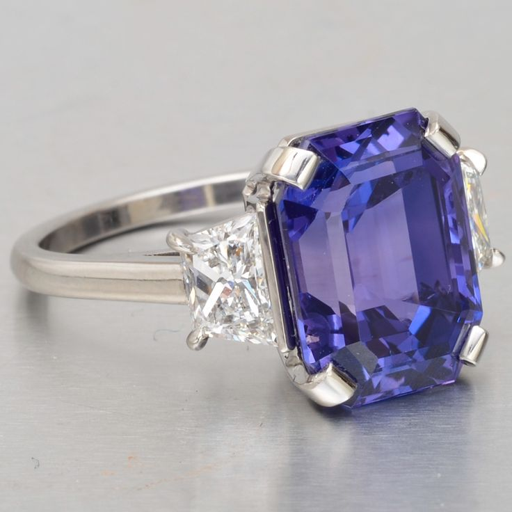 Emerald cut purple sapphire and diamond ring set in platinum with radiant cut diamond side stones. GIA certified natural sapphire, 8.54 carats