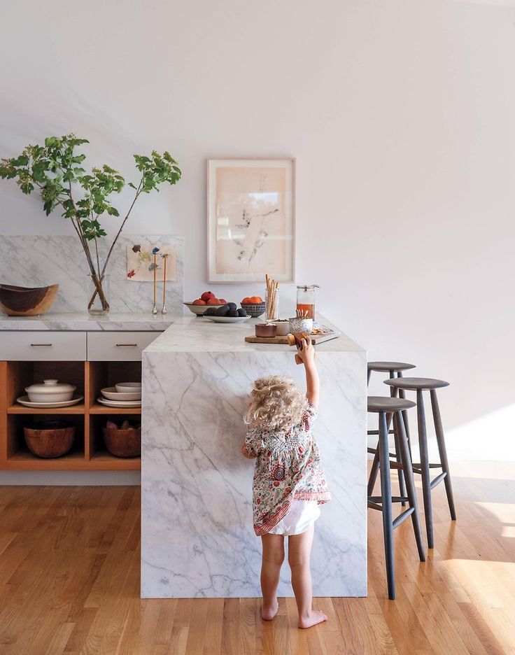 In the kitchen, Carrara marble transforms the dining peninsula into an eye-catching focal point.