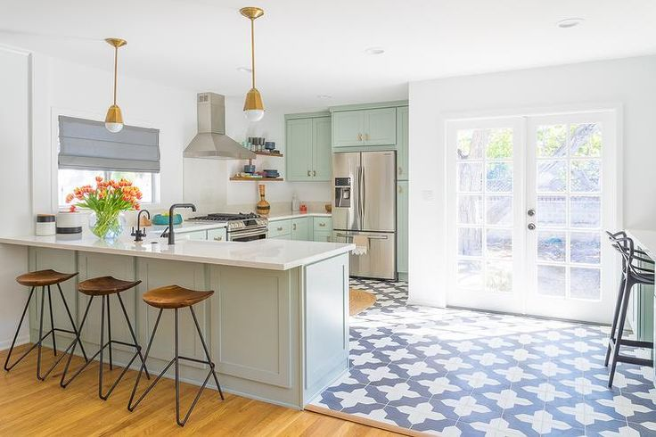 Contemporary kitchen features mint green cabinets adorned with brass hardware paired with off white quartz countertops and backsplash.