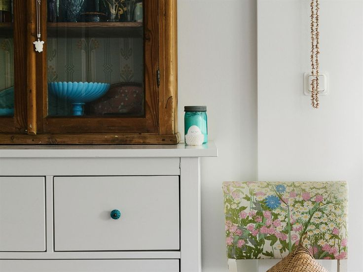 I hallen står en byrå från Ikea som målats vit och fått udda knoppar från Indiska. Ovanpå står ett vitrinskåp från Teds barndomshem.