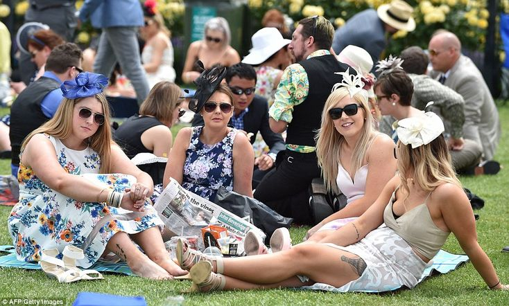 A group of woman take a load off and relax with a picnic on the lawns of Flemington Racecourse on Melbourne Cup Day
