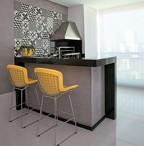 Como apoio para a churrasqueira, da Construflama, a arquiteta Ligia Resstom fez a bancada em L de granito preto e base cinza. Na parede, ladrilho hidráulico. O estofado amarelo dos bancos altos Bertoia contrasta com os acabamentos pesados da varanda