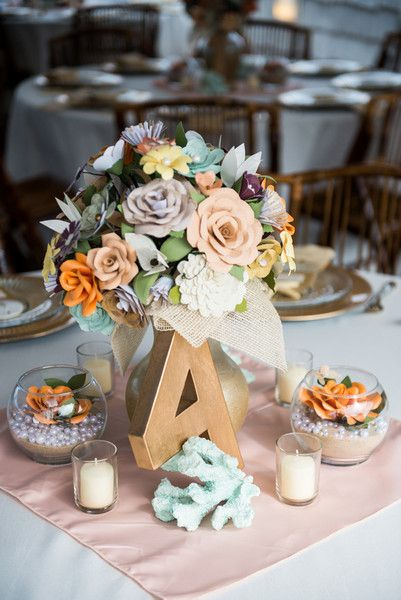 Love this pastel decor surrounding the gilded table numbers! Paper blooms, mint sea coral and mini glass bowls filled with pearls and paper roses. {@dkpullen}