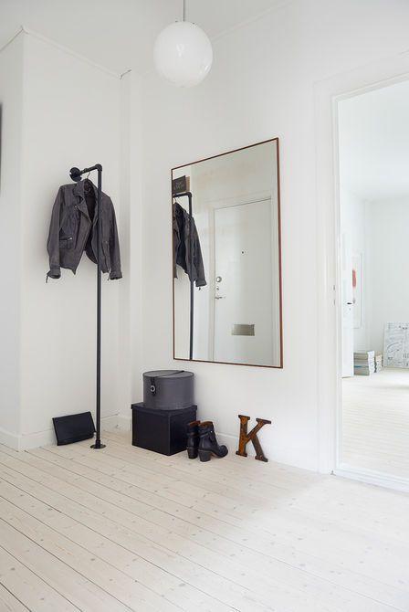Chociaż hol wcale nie jest mały mieści wyłącznie to, co niezbędne. Jest zatem czarny wieszak z metalowych rurek , duże kwadratowe lustro w drewnianych cienkich ramach, szare i czarne pudła oraz prosta lampa z mlecznym kloszem. Do białych ścian dobrze pasuje drewniana podłoga z pobielonych desek.