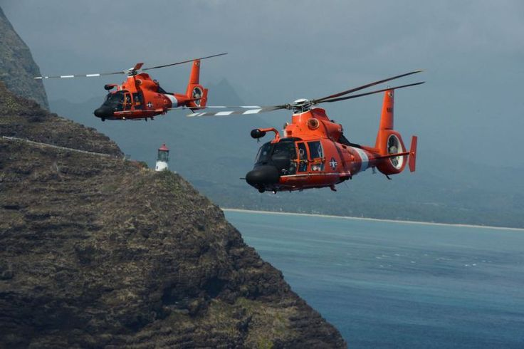 Two MH-65 Dolphin helicopter crews from Coast Guard Air Station Barbers Point conduct a practice formation flight around the Island of Oahu, March 4, 2016. The Dolphin aircrews along with an HC-130 Hercules aircrew practice proficiency with multiple aircraft flying at once. (U.S. Coast Guard photo by Petty Officer 2nd Class Tara Molle/Released)
