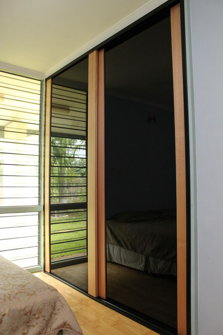 Tasmanian Oak, Frameless black glass. Sliding doors at their most simple and elegant. https://www.formfunctionnt.com.au/