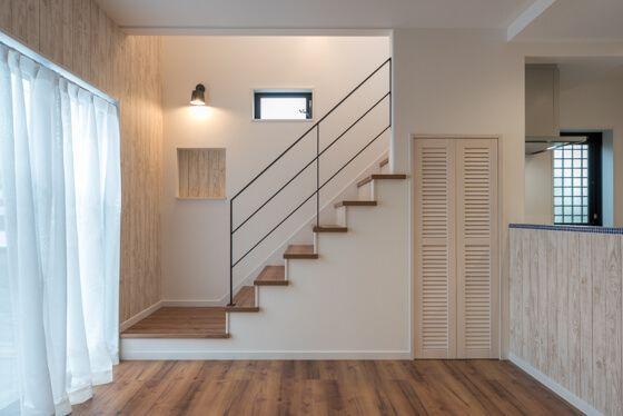 リビング階段は、造作のオープン階段。アイアンブラックの手すりと、ホワイト木目のルーバー扉(ウッドワン・ピノアース)の醸し出す雰囲気が、ナチュラルモダンな空間にとても似合っています