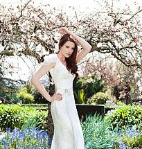 V-neck corded lace slim-line bridal gown with small train. Bella silk georgette frill sleeves and waist tie.