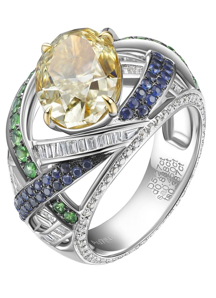 FANCY YELLOW DIAMOND RING  Bold, striking and delicate is this Fancy Yellow Diamond Ring. A sea of blue sapphire and green tsavorite, with a weave of white baguette diamonds, surround the majestic yellow diamond. The intricacy of this design represents lightness and daintiness.  FANCY YELLOW DIAMOND RING  Bold, striking and delicate is this Fancy Yellow Diamond Ring. A sea of blue sapphire and green tsavorite, with a weave of white baguette diamonds, surround the majestic yellow diamond.