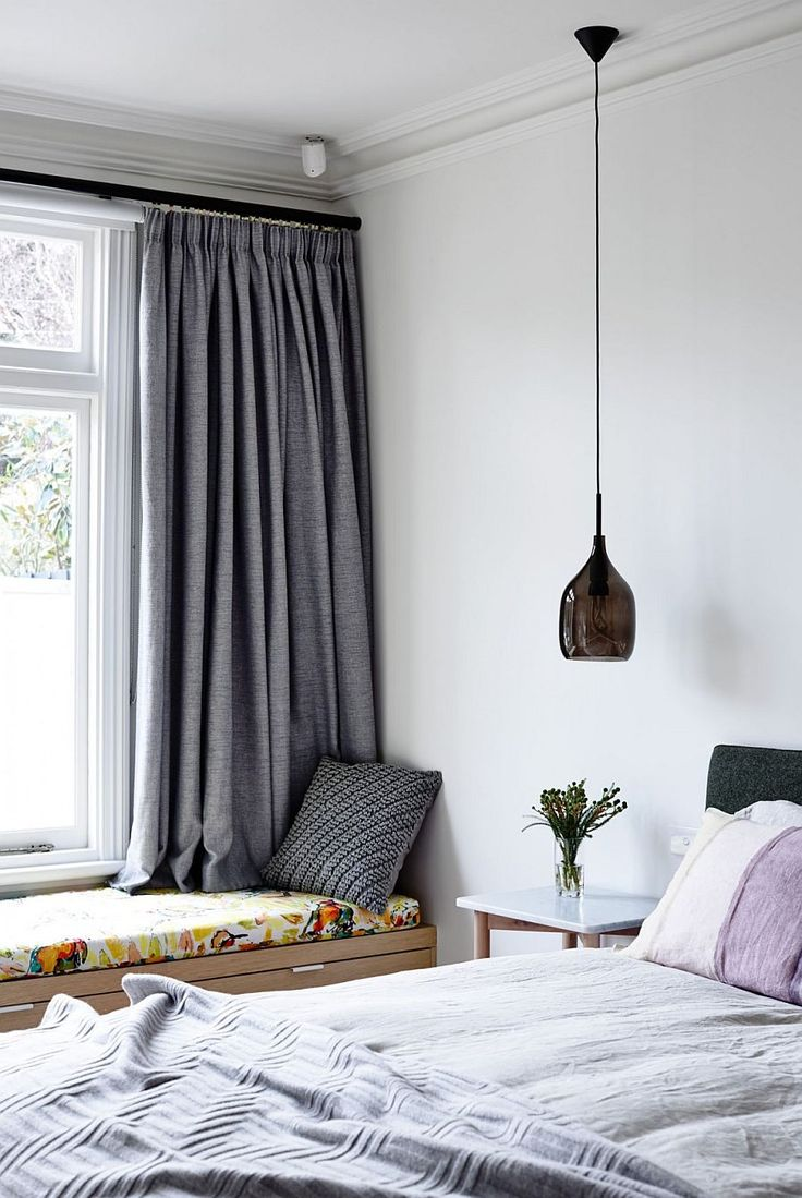 Chic contemporary bedroom with bedside pendant lighting and window seat