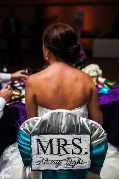 Embellish plain chairs with covers, signs, or flowers to mark your seats as the guests of honor.Photo Credit: Plum Tree Studios