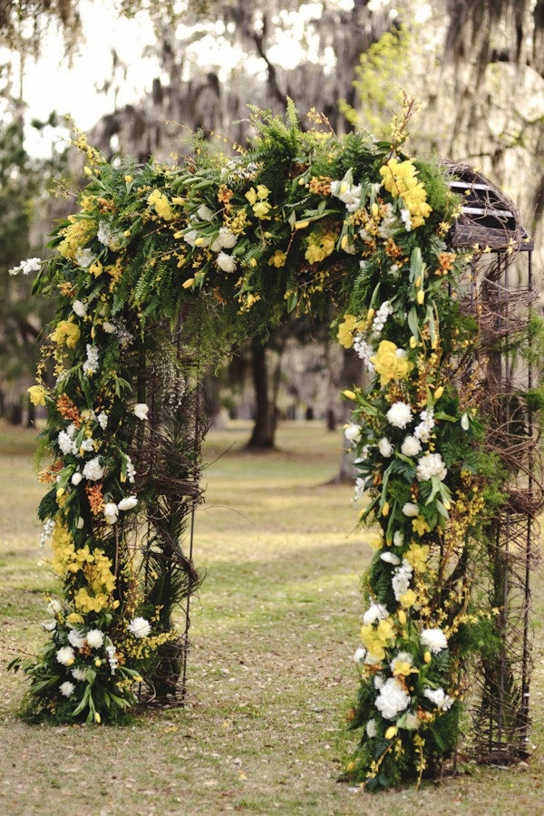 Pretty ceremony arch with yellow flowers