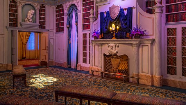 The candlelit Beast's library with a glowing fire in the fireplace at Enchanted Tales with Belle