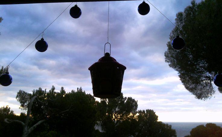Decorazione sul vetro della finestra (Salone Breakfast) lanterna con lumino e palline natalizie, fissate con filo di rame Sullo sfondo il golfo di castiglioncello