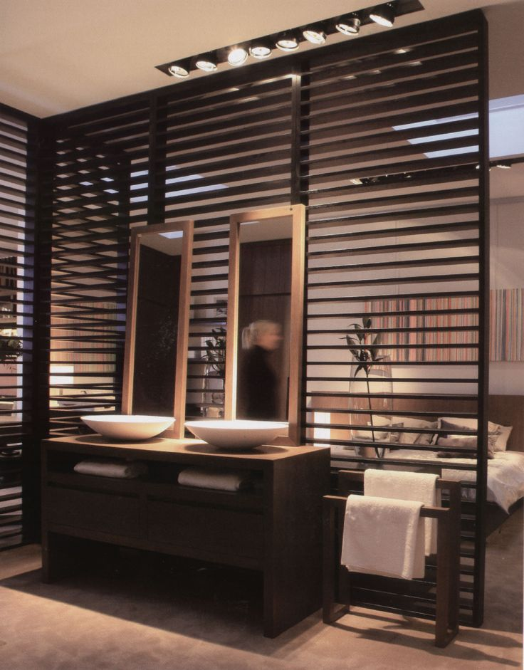 Wooden slat partition wall between bathroom and bedroom with dark timber furniture and mid tone floor