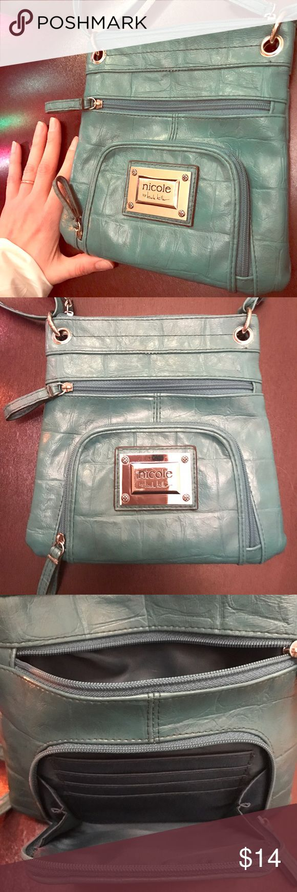 Nicole Miller teal purse Cute real purse with front zippered pocket, room for 4 credit cards. Zippered pocket on back, 4 zippered pockets in all. Shoulder or cross body worn. Gently used, no stains or visible wear. Nicole by Nicole Miller Bags Crossbody Bags