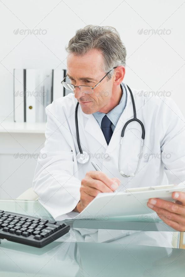 Concentrated Male Doctor Writing A Report At Desk In
