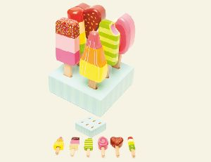 """The Ice Lollies Set from Le Toy Van's Honeybake Playset range offers children hours of tea party playtime. This Ice Lollies Set gives them everything they need for play time.  This new addition to the honeybake collection includes 6 brightly painted solid rubber wood """"ice-lollies"""" complete with a wood holder & presented in a colour window box."""