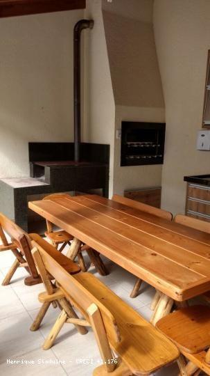 Espaço para reuniões com churrasqueira rotativa e fogão campeiro.