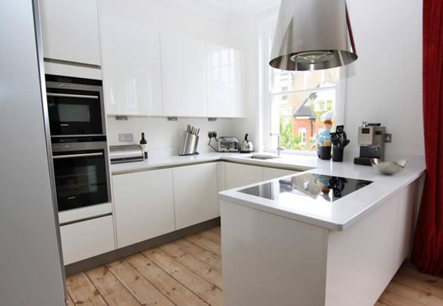 Your kitchen may be small but this doesn't rule out the possibility for including a kitchen island or peninsula within your design!  This handleless high gloss white kitchen designed by LWK Kitchens is perfect for the open plan layout; the peninsula introduces extra storage space, additional worktop space and an area that might also be used for extra seating. #smallkitchen #smallwhitekitchen #lwkkitchens