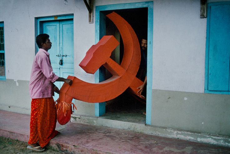 Steve McCurry, INDIA. Kerala, 1996. Two men push hammer and sickle indoors.                                                                                                                                                                                 More