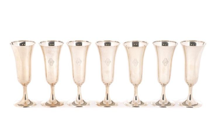 "Whiting Manufacturing Company (American (New York), 1866-1926), circa 1918. A matched set of fourteen sterling silver champagne flutes, each with monogram to circular foot. Hallmarked to the underside for Whiting Manufacturing Company, ""STERLING/2669"" and date code for 1918. Approximate height 6.5"", overall approximate weight 44.66 troy ounces."