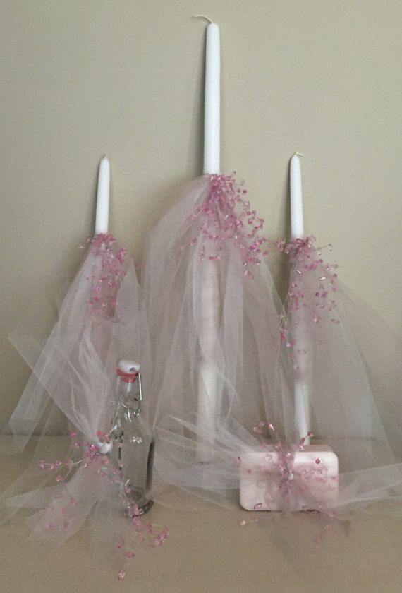 Beautiful elegant girly Baptism set. Decorated with ivory and nude tulle with a splash of pink crystals. Set includes: 1 - 24 inch candle 2 - 17 inch candles 1 - bar of soap 1 - oil container (oil not included) Also available with clear crystals.