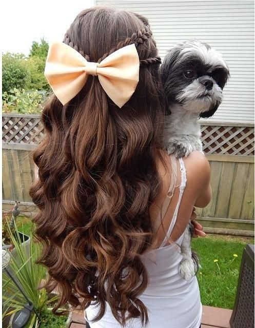 Half up half down hairstyle with curls and braids leading to a big bow