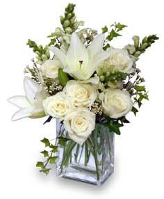 A lovely white arrangement will go with anything and is always elegant. White lilies, roses and other assorted flowers in this reusable cube. Perfect! Just give us a call 803-566-3204.