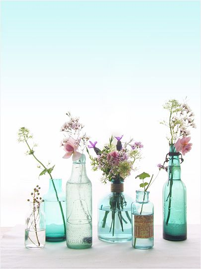 Using a group of small bottles as vases - very casual and rustic.