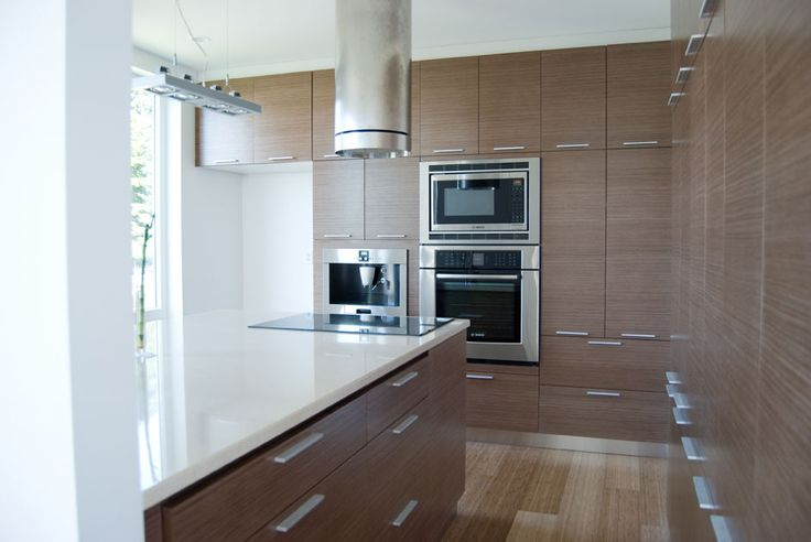 Floor to ceiling Quartered Walnut Echowood veneer cabinet doors, horizontal grain kitchen cabinets combined with white countertops and walls.