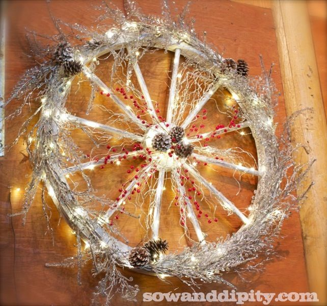 This wagon wheel makes a great wreath when all done up in silver picks, red berries and frosted pines cones. Such a great way to decorate a barn or old farm house! - #CowgirlChristmas #CountryChristmas
