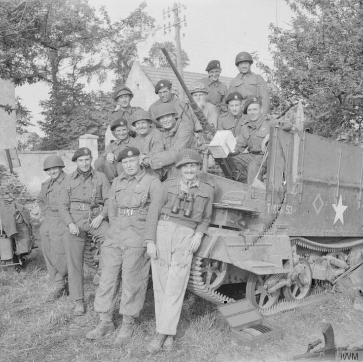 Men of the Staffordshire Yeomanry crowd in and around a universal carrier for a portrait, 7 June 1944. The vehicle is equipped with a .50-inch Browning machine gun, 7 June 1944.