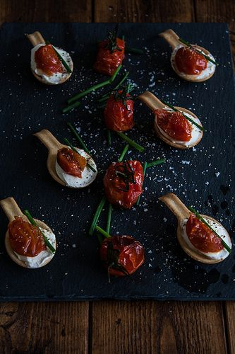 Canapes; edible spoons with cream cheese, half roasted tomato and a snip of chive scattered with sea salt and fresh ground black pepper.