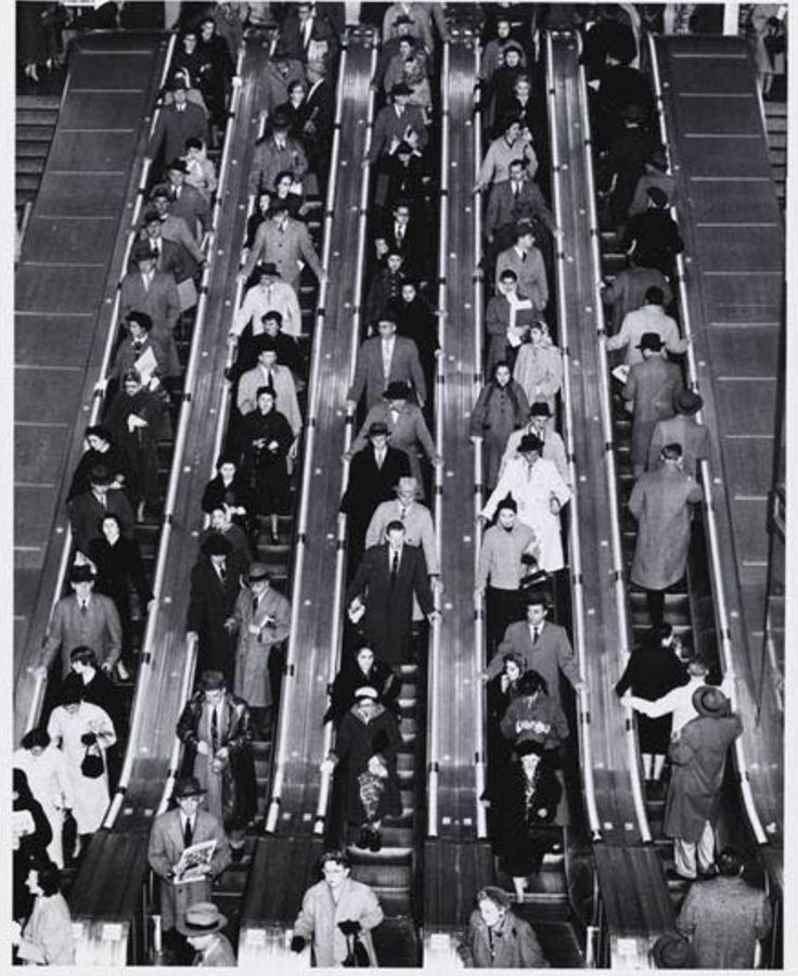 1955. 40th to 42nd St. between 8th and 9th Ave. Port Authority Bus Terminal. Commuters on the escalator. MCNY