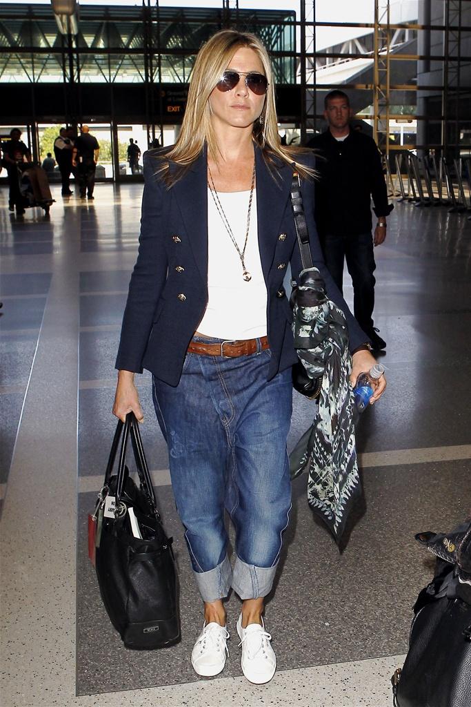 Jennifer Aniston apuesta por el fit boyfriend para viajar, ancho y cómodo para las largas horas de vuelo.    El carácter casual del vaquero se complementa con su americana de doble botonadura.