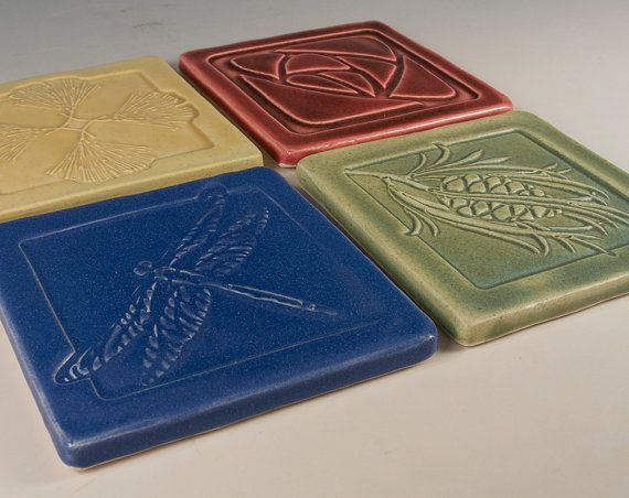 Hand rolled and pressed earthenware set of 4 tile coasters. Designed in the arts and crafts mission style for your bungalow or prairie style home. Slight color and size variations may occur on handmade tiles. Each coaster comes with protective cork backing.  size: approx. 4 1/4 x 4 1/4 each - 1/4 thick  Glaze - 4 assorted colors  craftsman style relief imprints  See our complete pottery listings at: http://www.etsy.com/shop/SeizPottery  Like Us on Facebook for advanced notice on new items: