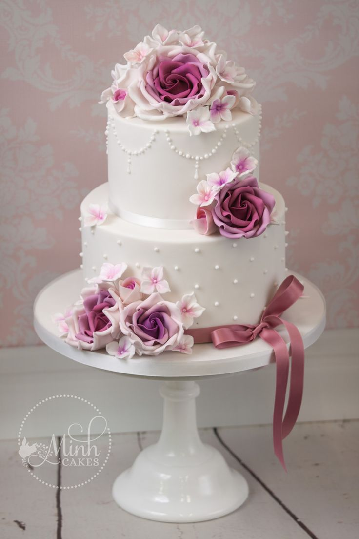 Cute two-tier wedding cake with purple roses. By …