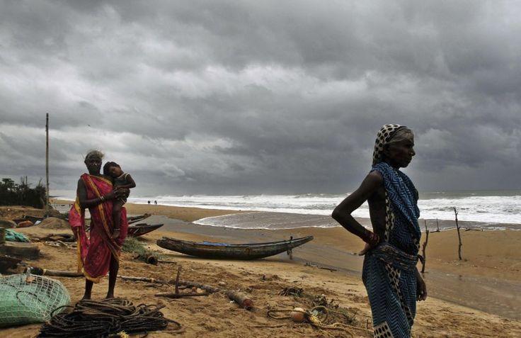 """Pescari din Podampeta, India privesc valurile mării înainte de a fi evacuați din calea ciclonului """"Hudhud"""""""