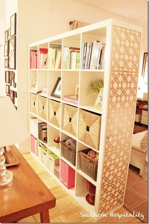 A brilliant room divider, the IKEA Expedit bookcase comes in handy for lots of storage and as a visual dividing line between bedroom and living room.  Love the grids on the end.
