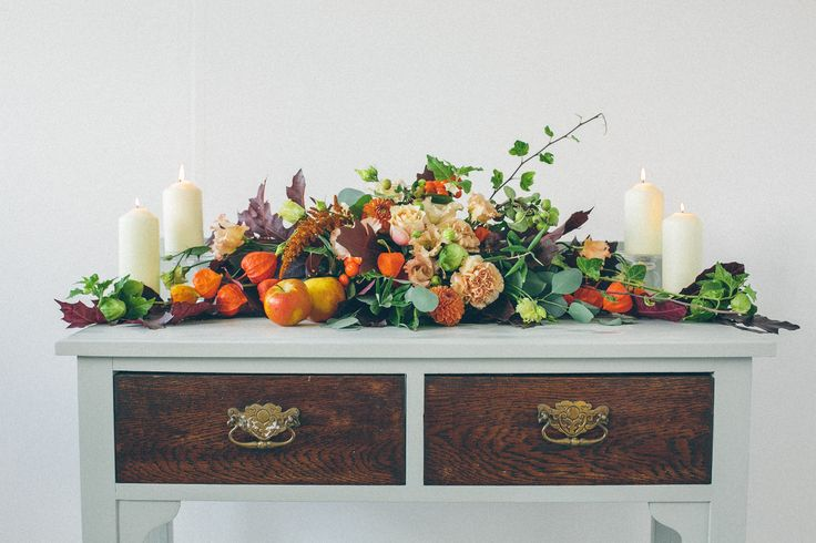 Autumn arrangement with fruit suitable for a ceremony or top table in orange, yellow, burgundy, wine, marsala wedding flowers. Captured by Ellie Grace Photography