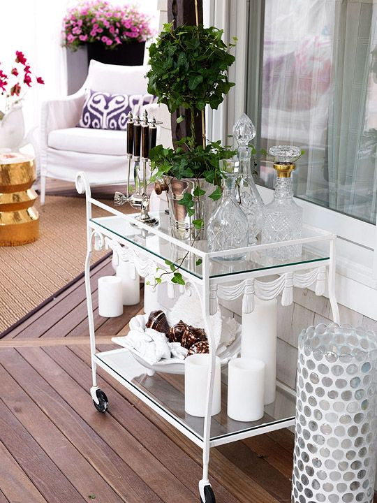 Freshen up the outdoor wrought iron cart with white paint and glass shelves, add bar glassware and tools to make a portable bar.   Pretty Porches and Terraces
